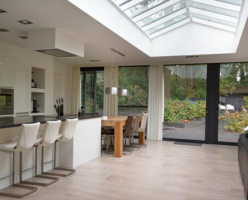 Een uitbouw met zadeldak lichtstraat. Een fijne open ruimte met daarin een leefkeuken en de woonkamer