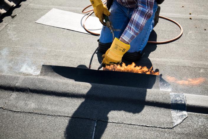 De dakdekker maakt het platdak waterdicht