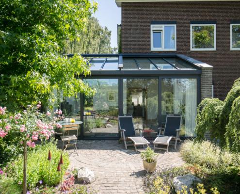 Serre aanbouw in antraciet kleur met een glazen dak en een vierdelige schuifpui, een lekker terras om te genieten van de zon