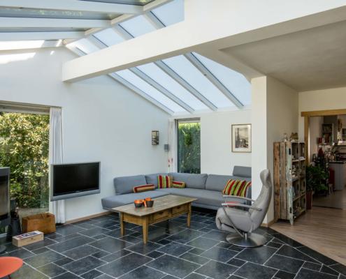 Aan het woonhuis is een grote lichte aanbouw geplaatst waar veel gebruik is gemaakt van glas, in het dak en de elementen rondom