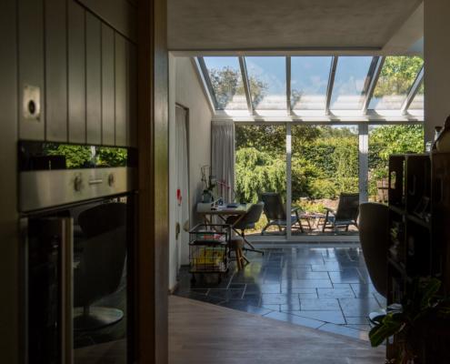 Een doorkijkje vanuit de keuken naar de woonkamer met serre aanbouw